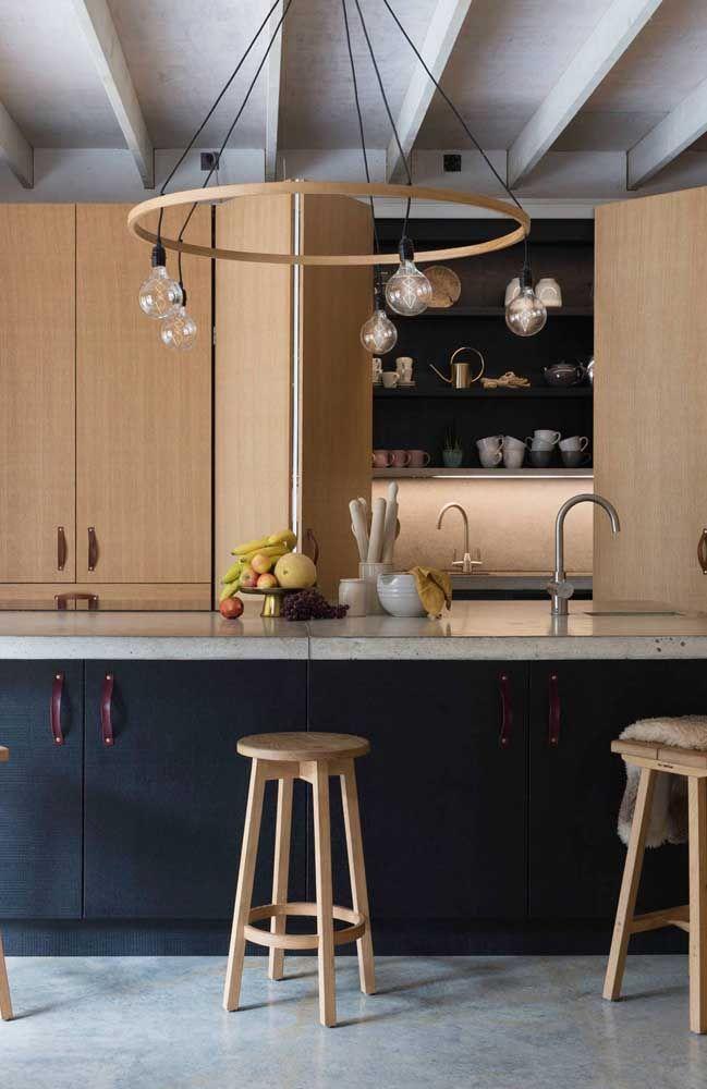 O material do lustre implica diretamente no visual da cozinha, esse aqui, por exemplo, foi feito em madeira seguindo o padrão de cor e textura do armário