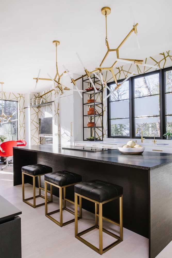 O lustre dourado completa com elegância a decoração da cozinha em tons de preto e branco.