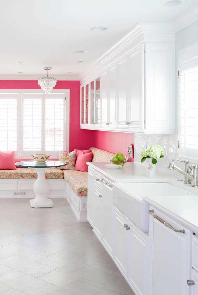 Nessa cozinha, o pequeno lustre de cristal foi usado de modo decorativo sobre a mesa de jantar, a iluminação principal é feita pelas luminárias embutidas no teto