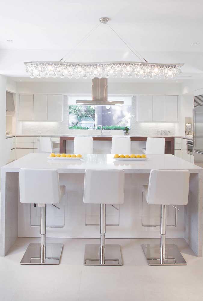 A cozinha branca reforça ainda mais a claridade que sai do lustre alongado sobre a mesa