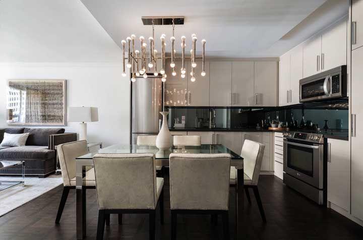 Modernidade e elegância definem esse lustre sobre a mesa de jantar