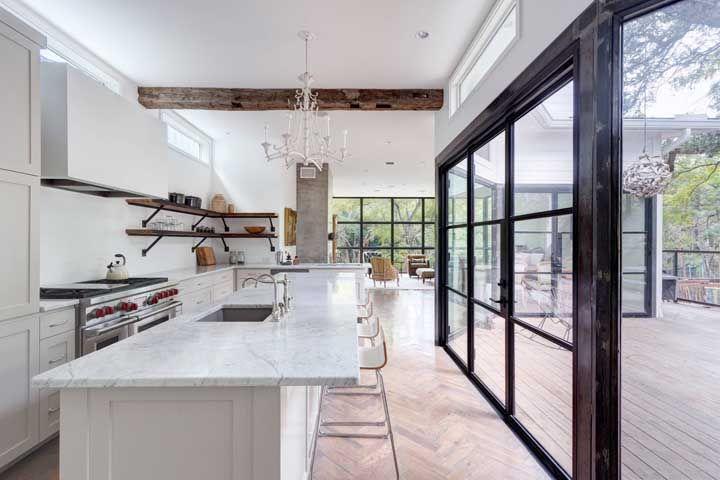 O rústico e o clássico se encontram nessa cozinha, passando pela viga de madeira exposta e o lustre branco de cristal