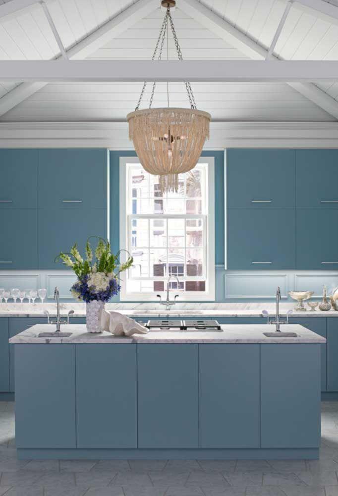 A cozinha azul e branca apostou em um grande lustre sobre a ilha, coroando o ambiente com muita elegância