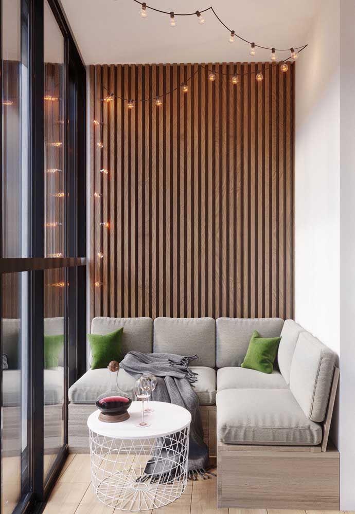 Sacada de vidro com portas inteiriças de correr; o visual da sacada fica mais completo com o revestimento de madeira