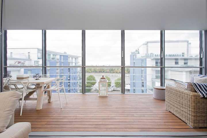 O vidro permite que a área externa se una a parte interna da casa, mas a diferenciação dos ambientes ainda é notada pelo piso