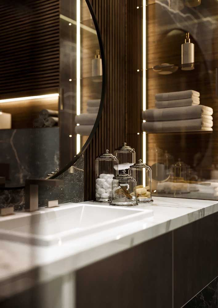 Os recipientes de vidro, simples e delicados, combinam perfeitamente com o dourado das paredes, criando um ambiente refinado e encantador