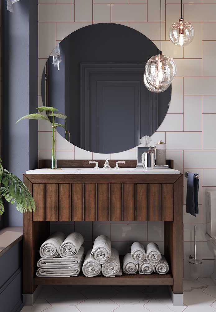 O kit de higiene simples foi suficiente para esse banheiro que esbanja elegância com a bancada de madeira