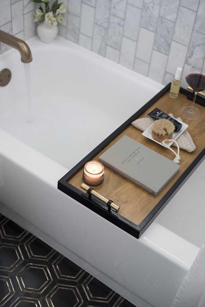 Aqui, o kit higiene foi colocado sobre a bandeja que se encaixa na banheira, formando junto com a taça de vinho e o livro, um conjunto ideal para aqueles momentos feitos para relaxar