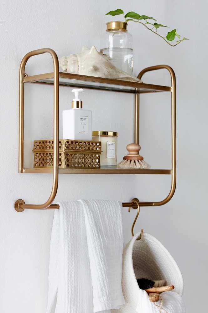 A prateleira de metal dourado na parede é ideal para quem não possui muito espaço e que também não deseja abrir mão da sofisticação