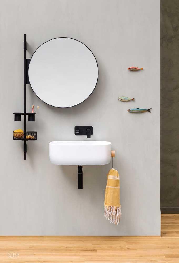Nesse banheiro, o kit higiene foi posicionado em uma haste de metal ligada diretamente ao espelho