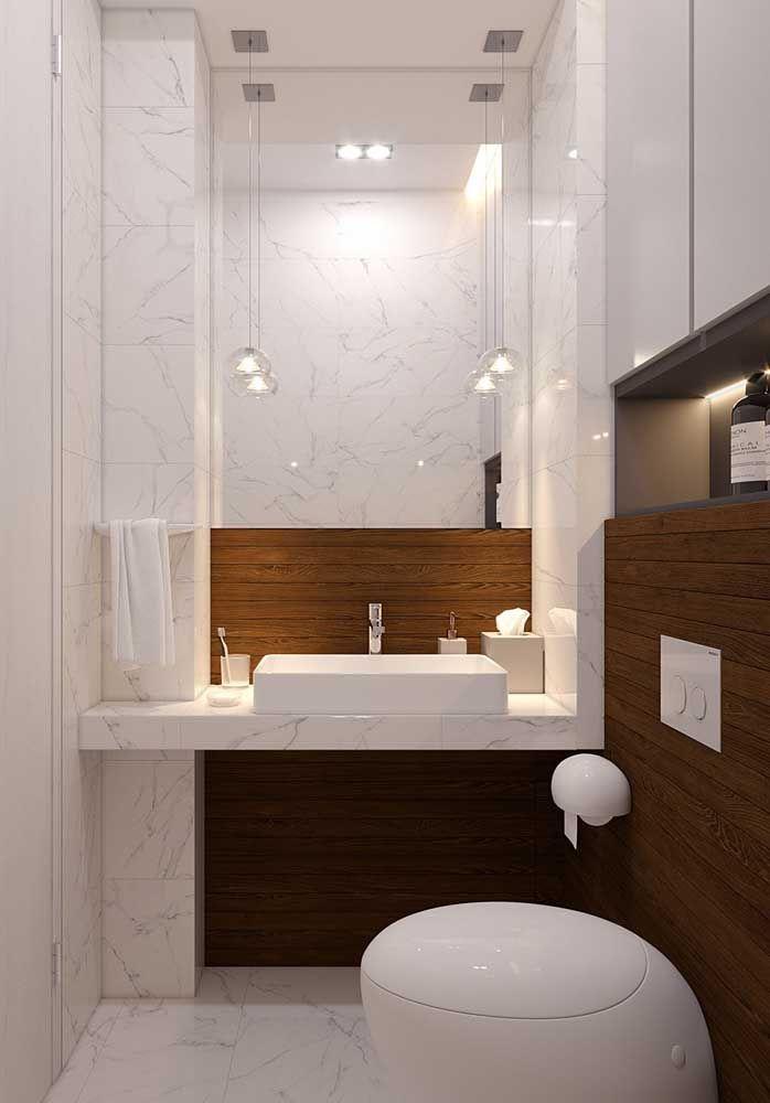 Sobre a pia, o kit não atrapalha a sutileza do banheiro que combina madeira com um refinado mármore