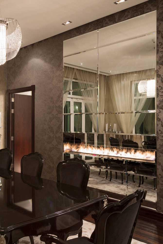 A sala de jantar clássica e elegante apostou em uma lareira ecológica embutida em meio a parede de espelhos, um luxo só!
