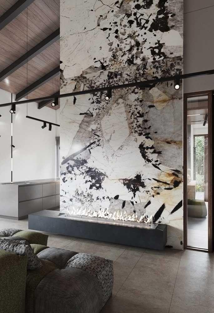 Nessa sala de pé direito alto, o lugar escolhido para a lareira ecológica foi rente ao chão e encostada na parede de maior destaque
