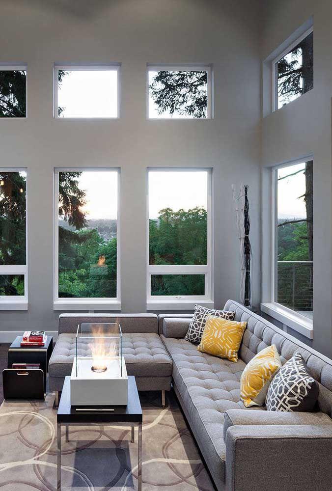 No centro da sala, a lareira ecológica expande o calor de modo mais equilibrado