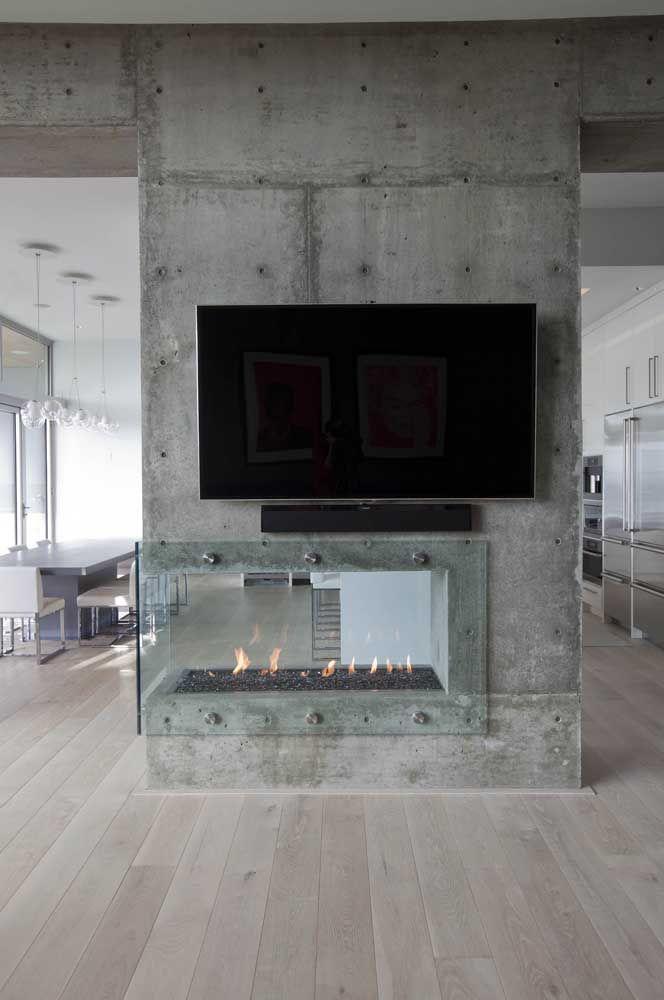 Aqui, a parede de concreto aparente foi usada como painel para TV e encaixe para a lareira ecológica