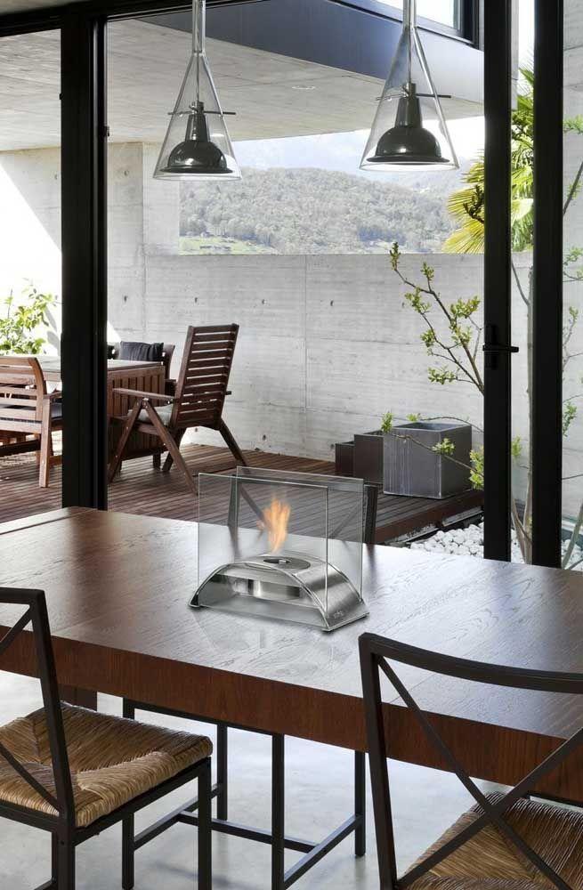 Pequena, essa lareira ecológica portátil foi colocada sobre a mesa de jantar, mas pode facilmente ser transportada para outros lugares da casa