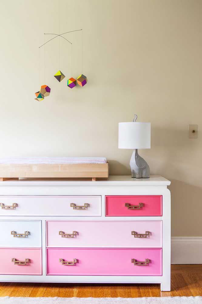 Nesse quartinho de bebê, aquilo que é indispensável para a funcionalidade do ambiente se tornou objeto de decoração, como o abajur em formato de elefante, o mobile colorido e a cômoda em tons de rosa