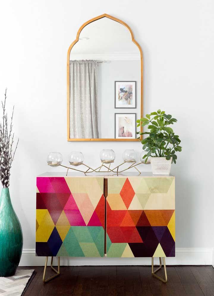 A presença marcante do aparador é valorizada pelo espelho de estilo clássico e os vasos ao redor