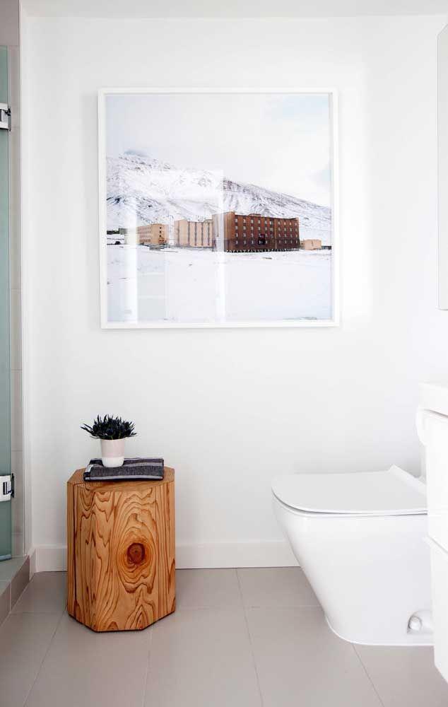 A brancura desse banheiro foi amenizada pelo tronco que serve como apoio para o pequeno vaso