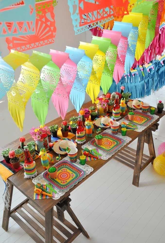 Suculentas e cactos sobre a mesa de cores alegres; logo acima, enfeites de papel