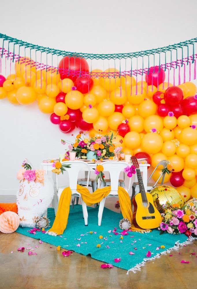 Arco desconstruído de balões e um violão a postos para animar a festa