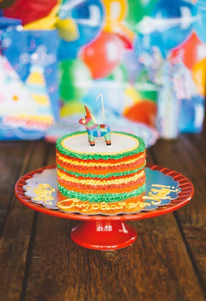 Camadas coloridas de chantilly e uma mini pinhata decoram esse pequeno bolo da festa mexicana
