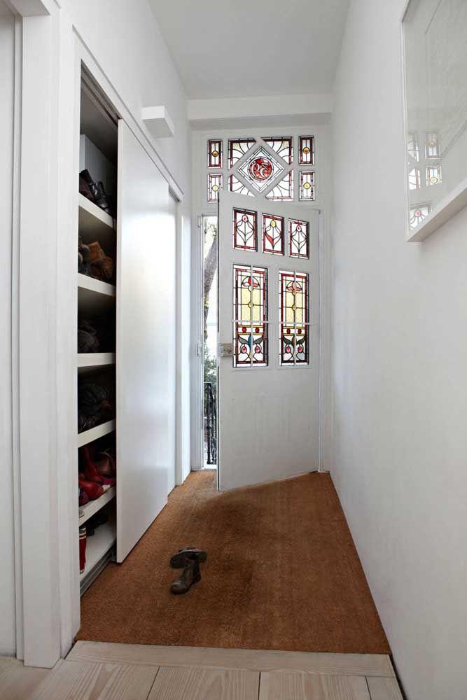 A porta de correr no hall de entrada esconde uma sapateira de inúmeros pares