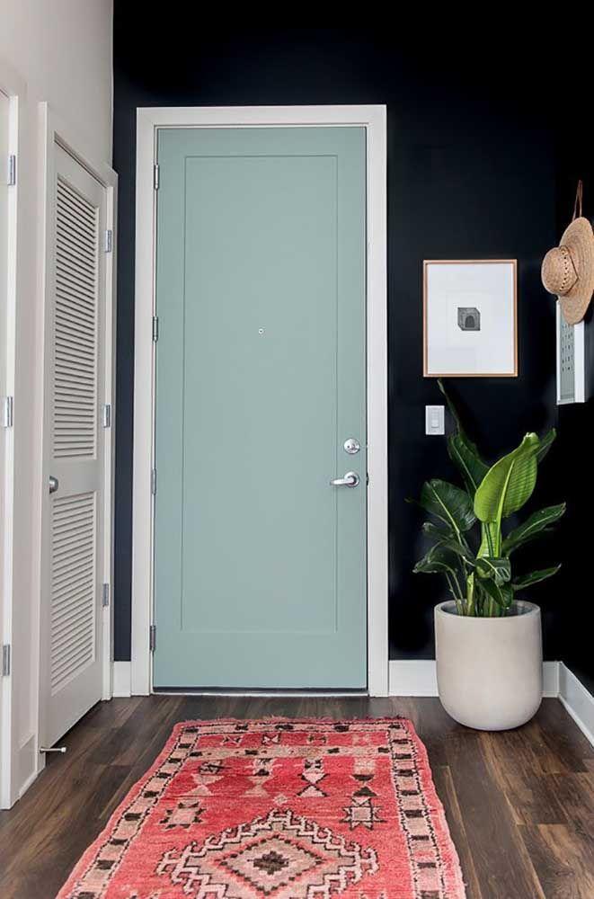 Uma entrada de casa marcante: paredes escuras com porta azul claro; destaque para o batente branco que se harmoniza diretamente com a parede ao lado