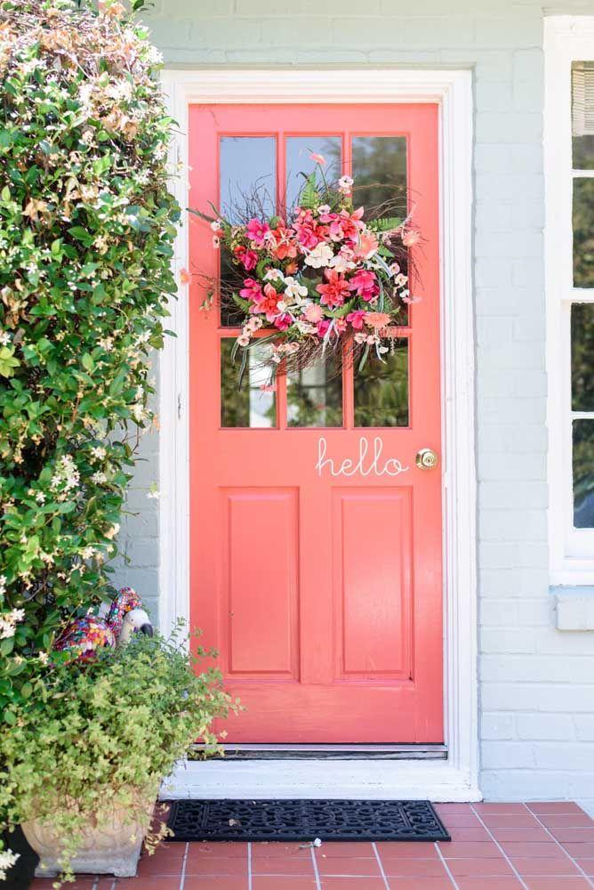 Para completar o visual dessa porta cor de rosa, uma guirlanda de flores naturais no mesmo tom