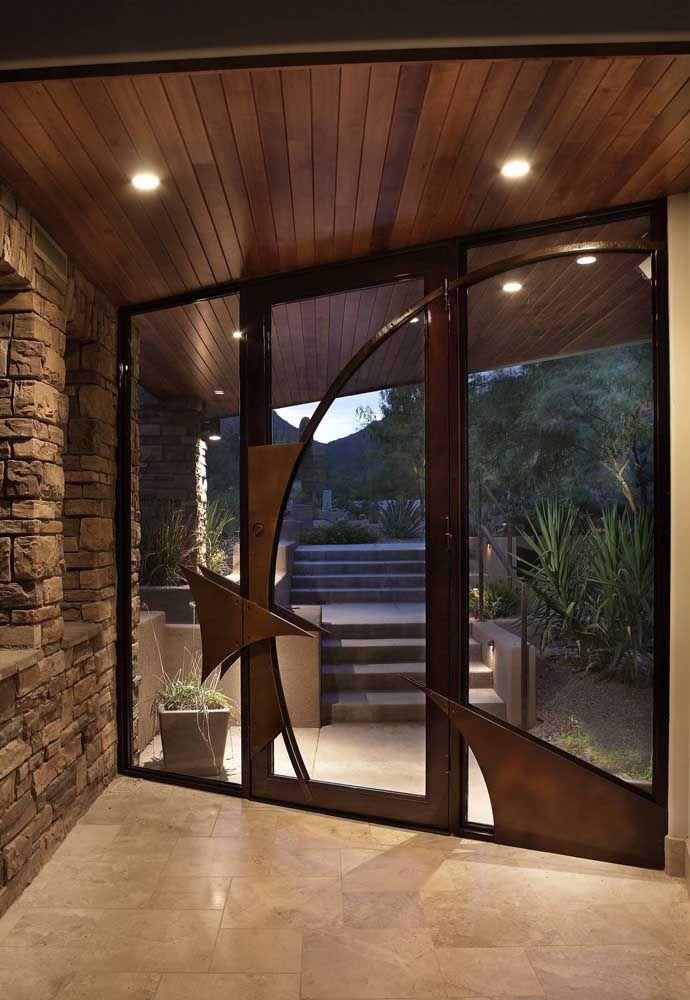 Hall de entrada para ficar na memória: aqui, o mix de materiais presente na parede e na porta é traduzido em conforto, acolhimento e sofisticação