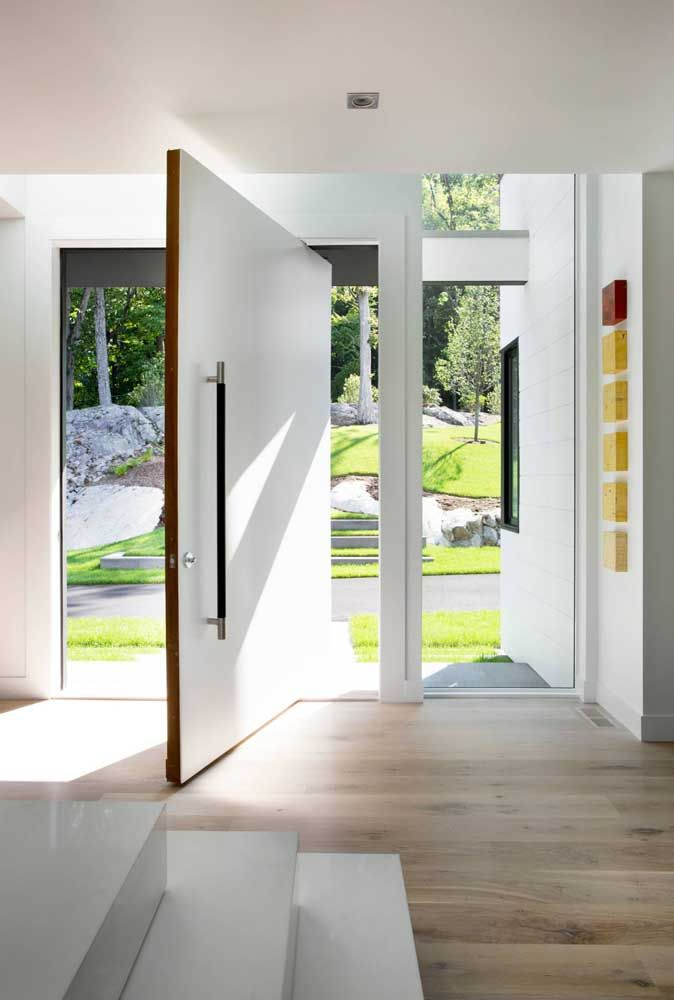 Olha essa inspiração de porta de entrada pivotante branca: muita elegância em um projeto só