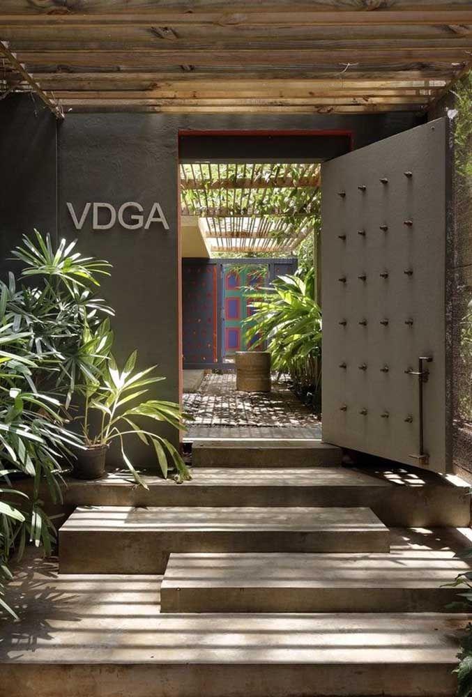 Porta grande, de concreto e cheia de estilo: um convite para adentrar e descobrir o interior da residência