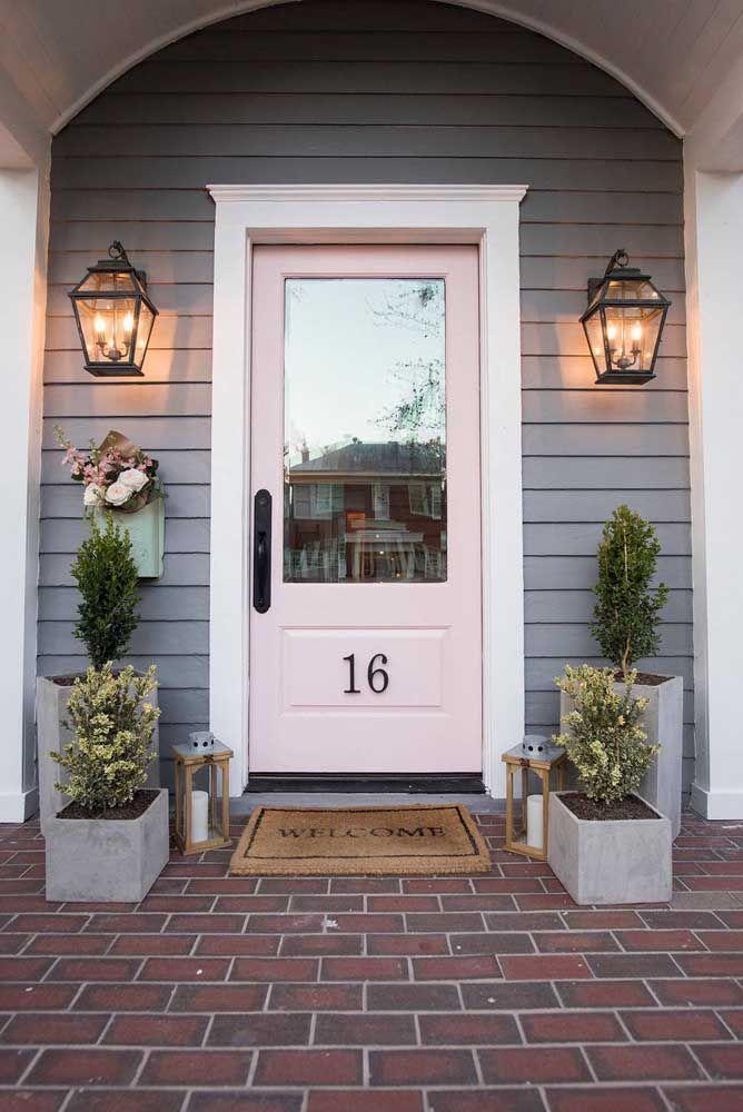 Aqui, o rosa também é a cor escolhida para a porta, mas em um tom bem mais claro e suave; destaque para as luminárias laterais que emolduram a porta