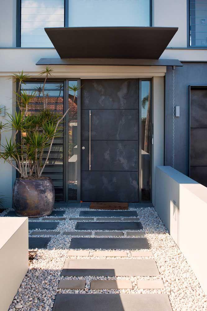 O que acha de uma porta de entrada de aço para destacar a proposta moderna da construção?