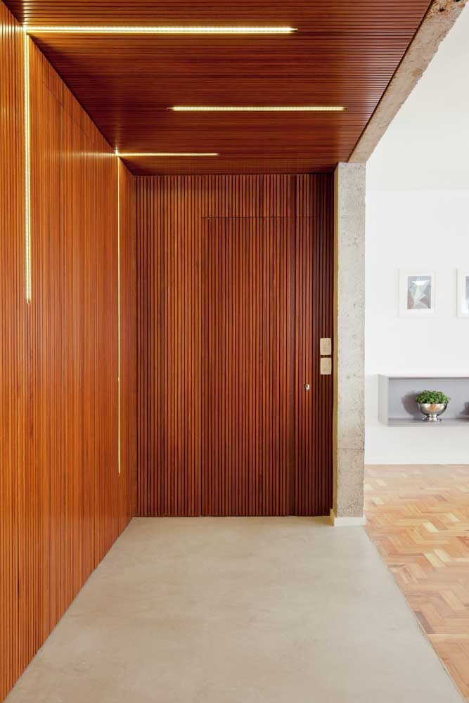 Nessa casa, a porta segue o padrão do revestimento da parede formando uma fachada uniforme