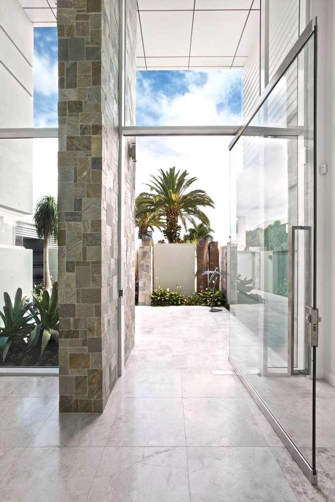 A porta de entrada de vidro é uma presença discreta e sutil nessa fachada