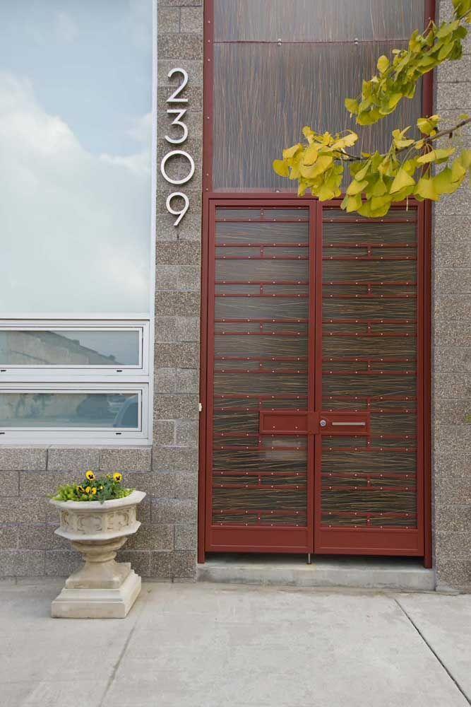 Vidro e aço formam essa porta de entrada que se funde ao revestimento da parede graças ao uso da mesma tonalidade