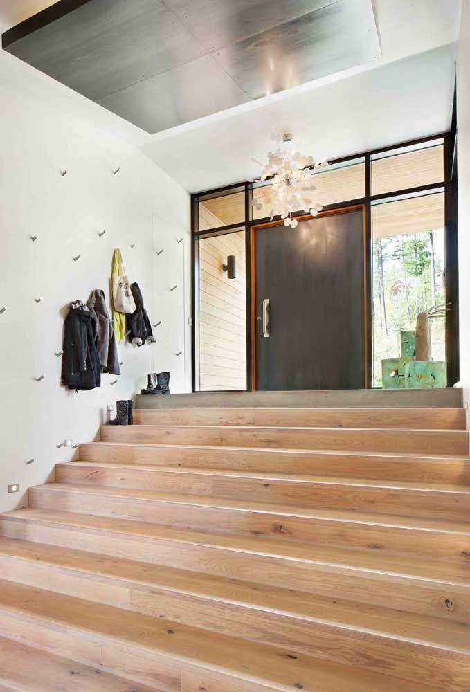 Ao final da escadaria, uma enorme porta de madeira recepciona quem chega