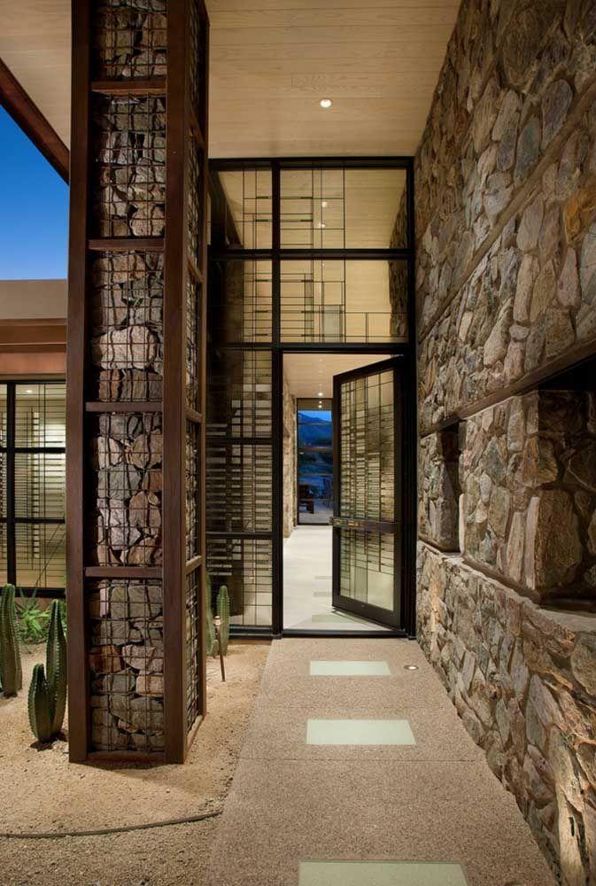 O corredor de pedras contrasta com a delicadeza da porta de vidro transparente