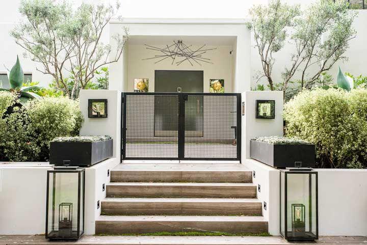 Nessa casa, a porta de vidro simples se esconde atrás do pequeno portão preto