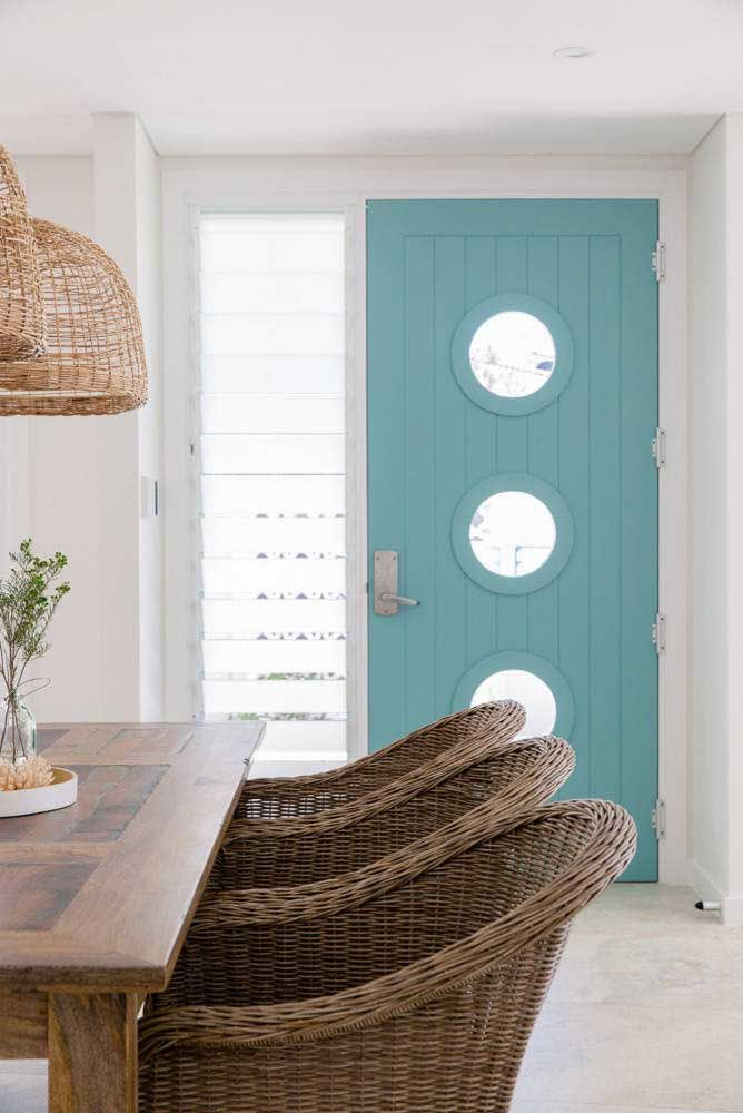 Os pequenos círculos na porta de madeira ajudam a levar uma iluminação melhor para dentro da casa
