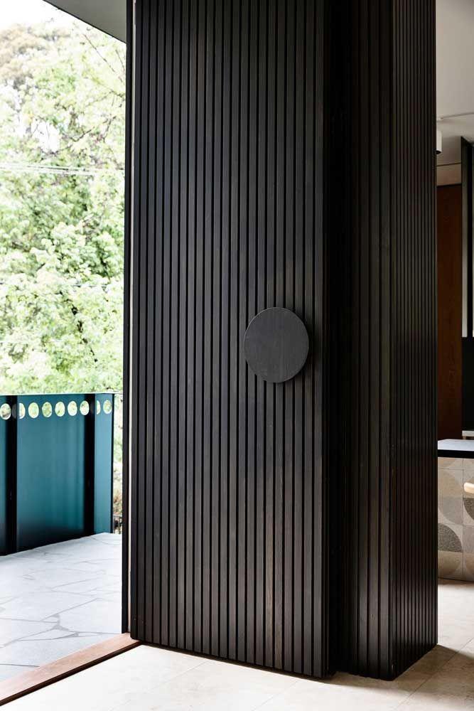 Mais alta que o normal, essa porta de madeira preta é um destaque e tanto na fachada da casa