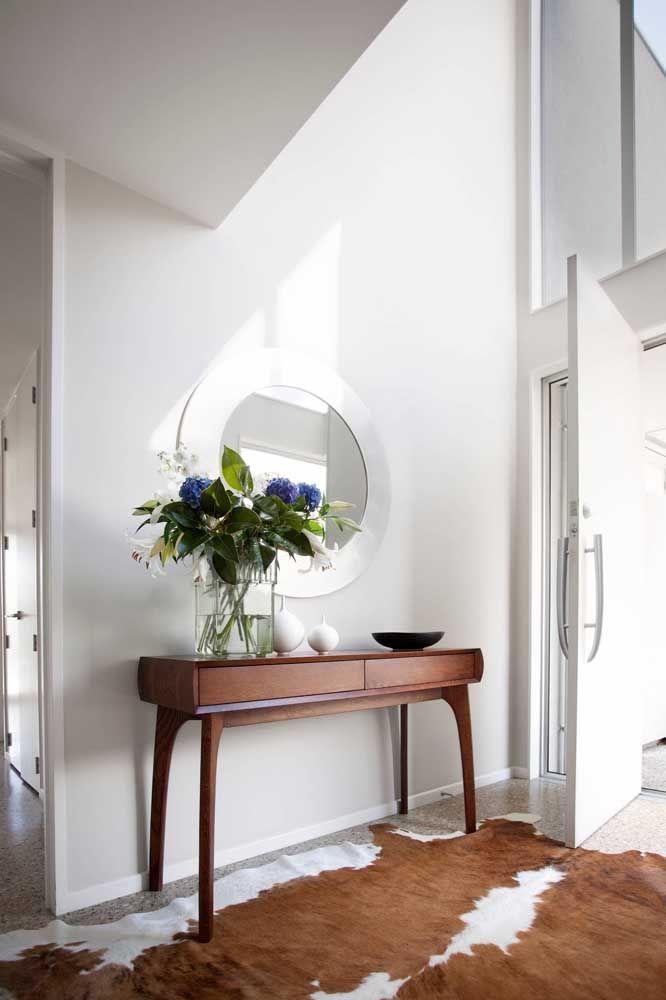 Outra opção de aparador na entrada da casa é esse modelo feito de madeira, mas com um design diferente. O espelho com a moldura na cor da parede fica bem suave e discreto.