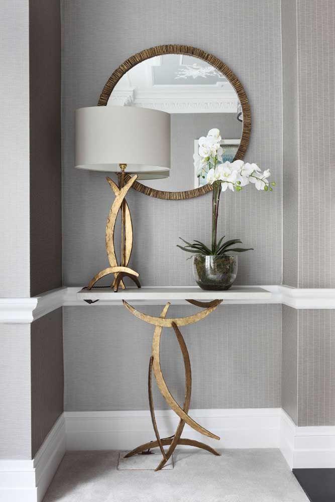 Aproveite o espaço entre um cômodo e outro para colocar o aparador com espelho. O pé do aparador combinando com do abajur acaba sendo o grande destaque da decoração.