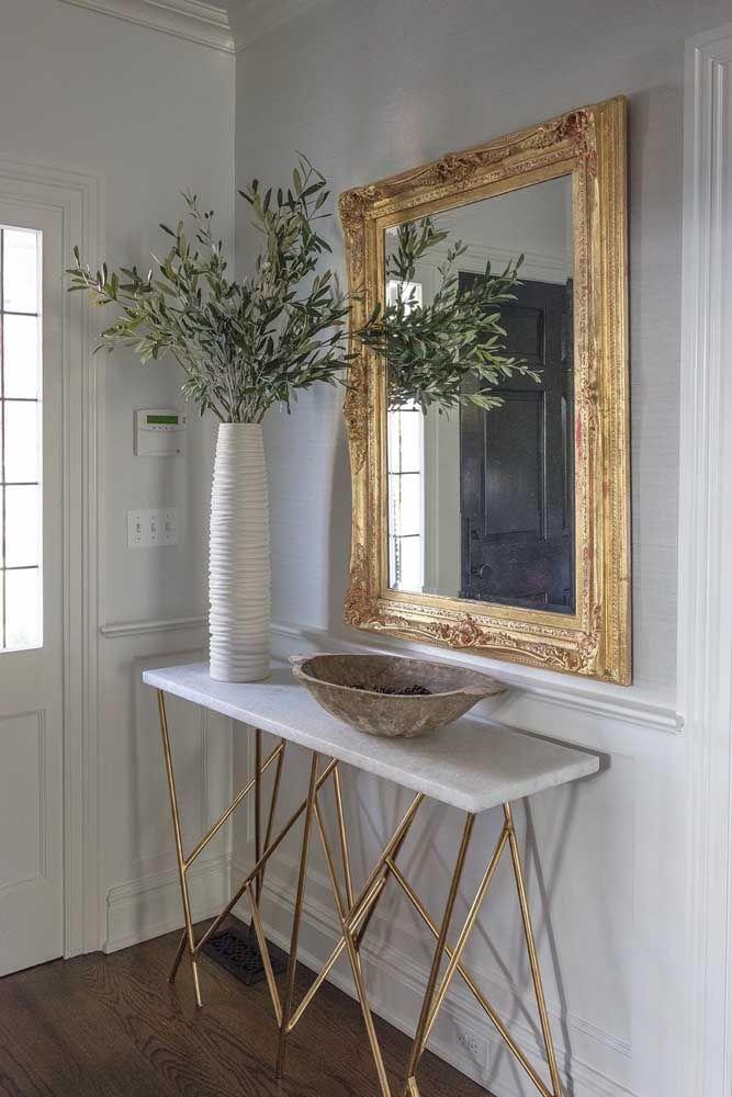 Mais um modelo de aparador para a entrada da casa. O modelo é feito com pedra de mármore sustentado por um pé feito de ferro dourado. O espelho com moldura dourada chama a atenção.