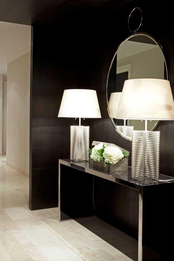 Para combinar com a cor da parede mais escura, use um aparador no mesmo tom e destaque o ambiente com um espelho e alguns elementos decorativos feitos de metal. Fica um luxo só!