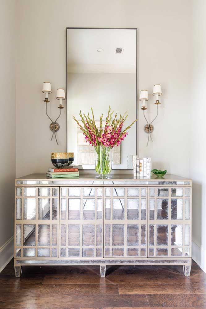 Escolha um aparador com detalhes em espelho e coloque um espelho simples para compor o cenário.