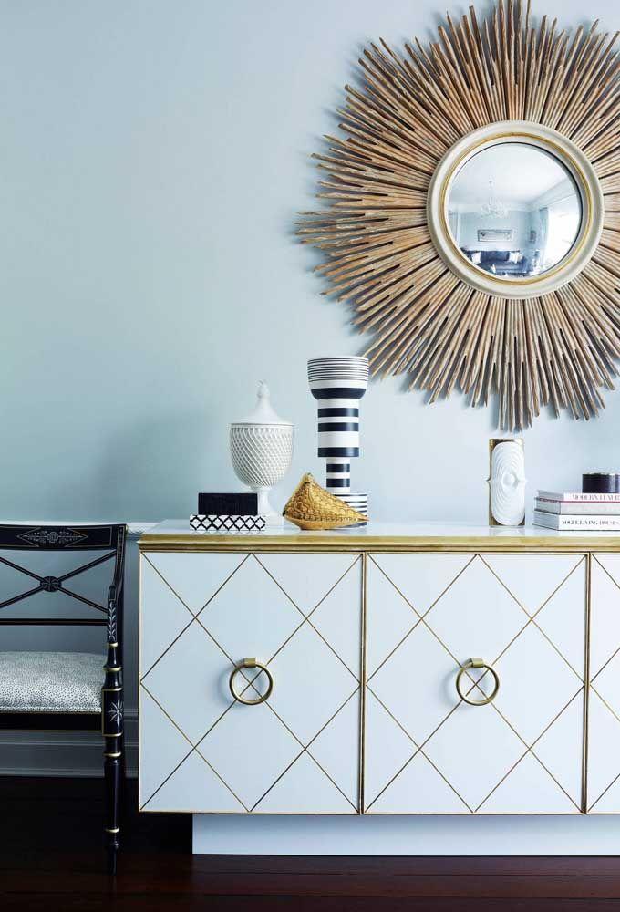 Use um aparador na cor branca com detalhes em dourado para combinar com o espelho de moldura totalmente dourada e diferenciada.