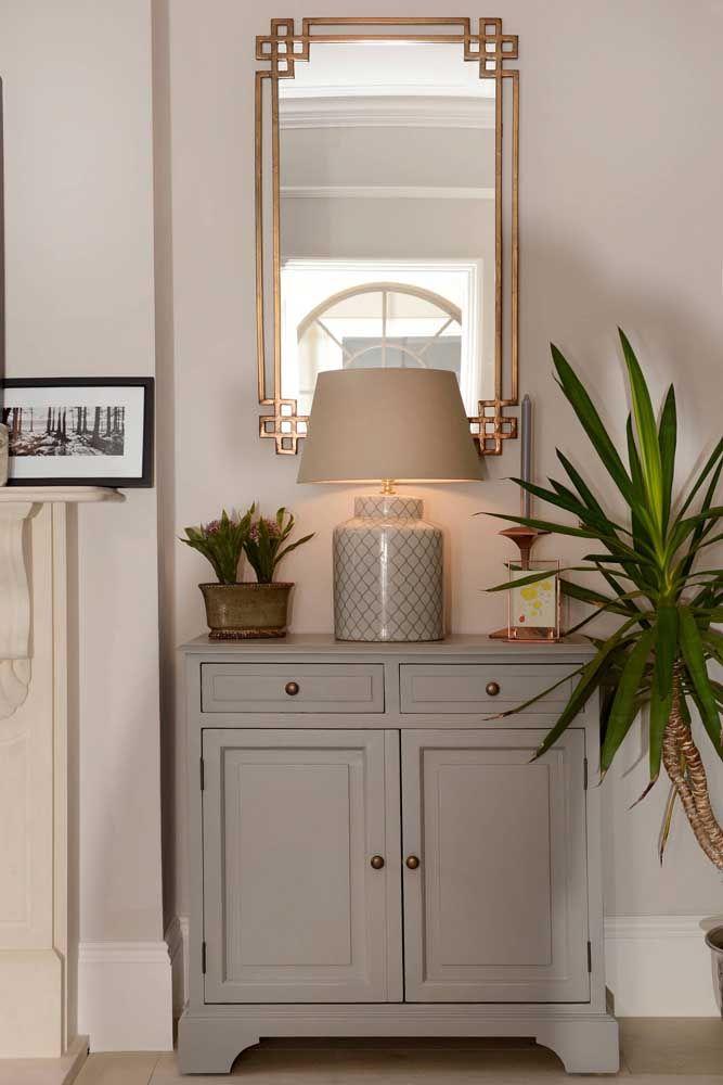 Para colocar um aparador em um cantinho da casa, use um modelo no formato de armário, mas que seja pequeno. O espelho pode ser retangular com moldura dourada para combinar com decoração.