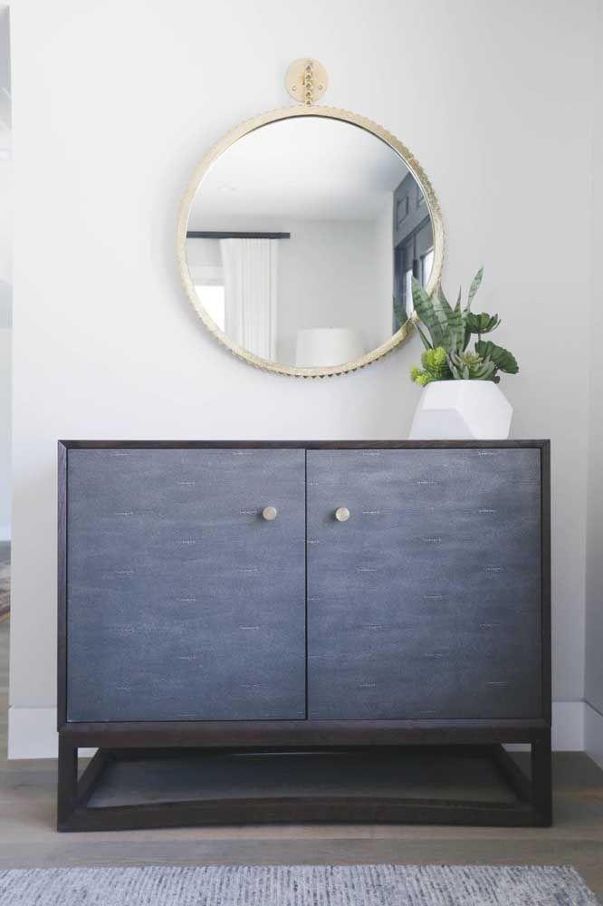 O aparador no formato de caixote com gavetas é ótimo para ambientes mais rústicos. Um espelho redondo simples dá o toque final.